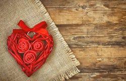 Coeur en osier rouge avec les roses et le ruban, serviette de toile Photos libres de droits