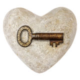 Coeur en pierre avec une clé de cru d'isolement sur le blanc Photo libre de droits