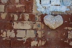 Coeur en pierre blanc sur un vieux mur de briques brun, symbole de l'amour, valentine Image stock