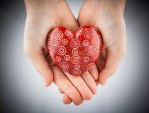 Coeur en pierre rouge chez des mains de jeune femme, vignette modifiée la tonalité Photographie stock
