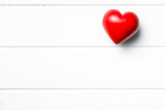 Coeur en pierre rouge sur le fond en bois blanc Image stock