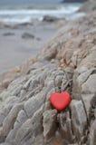 Coeur en pierre rouge sur le rivage rocheux photos libres de droits