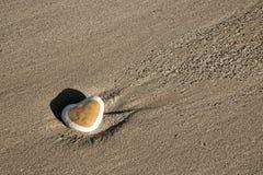 Coeur en pierre sur la plage Photos libres de droits