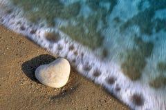 Coeur en pierre sur la plage dans les vagues Images libres de droits