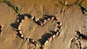 Coeur en pierre sur le sable humide et humide de la berge de ville une soirée ensoleillée d'été photo stock