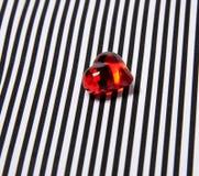 Coeur en plastique d'effet en verre clair sur un fond rayé noir et blanc Photos stock