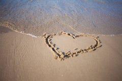 Coeur en sable à la plage, à la confession de l'amour, à l'été, à la mer et au soleil Images libres de droits