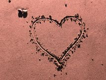 Coeur en sable rose photographie stock