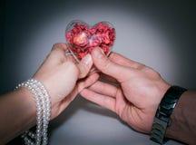 Coeur en verre avec les fleurs rouges à l'intérieur du ` s de femmes et de la main du ` s d'hommes Image stock