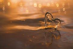 Coeur en verre clair sur la plage de sable avec la lumière du soleil de lever de soleil Photo stock