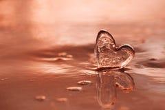 Coeur en verre clair sur la plage de sable avec la lumière du soleil de lever de soleil Image stock