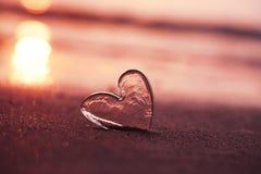 Coeur en verre clair sur la plage de sable avec la lumière du soleil de lever de soleil Images stock