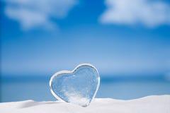 Coeur en verre clair sur le verre et le reflec blancs de scintillement de plage de sable Photo libre de droits