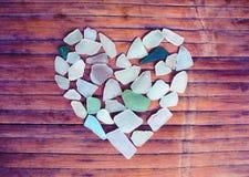Coeur en verre de bord de la mer sur le fond en bois Sucrez la mosaïque en verre pour le jour du ` s de Valentine Photographie stock libre de droits
