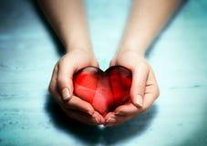 Coeur en verre rouge chez des mains de la femme Photo stock