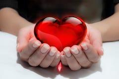 Coeur en verre rouge chez des mains de la femme photos libres de droits