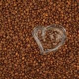 Coeur en verre sur des grains de café Photos stock