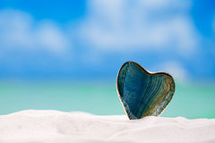 Coeur en verre vert sur la plage blanche de sable, image stock