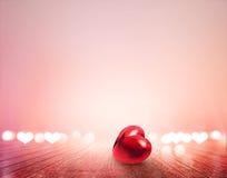 Coeur et bokeh rouges sur le plancher en bois vibrant pour le fond Photographie stock