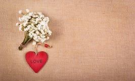 Coeur et bouquet en bois rouges des wildflowers blancs Fleurs et carte postale sur un fond de toile naturel Concept romantique Image libre de droits