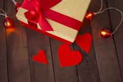 Coeur et cadeau de trois rouges sur un fond brun d'arbre avec des guirlandes Images libres de droits