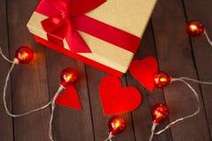 Coeur et cadeau de trois rouges sur un fond brun d'arbre avec des guirlandes Photos libres de droits