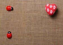 Coeur et coccinelle sur le tissu Image stock