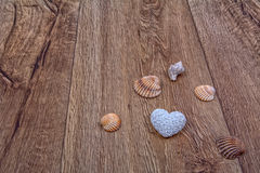 Coeur et coquilles sur un fond en bois Images stock