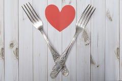 Coeur et couverts sur un fond en bois, panneaux lumineux, jour du ` s de Valentine Photos libres de droits