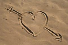 Coeur et flèche dessinés par sable Images stock