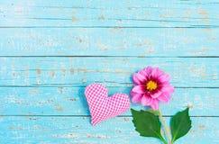 Coeur et fleur roses d'amour sur le bois bleu-clair Images stock