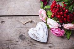 Coeur et fleurs décoratifs sur le fond en bois de vintage Photos stock
