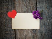Coeur et fleurs de papier des violettes sur une vieille feuille de papier sur le fond en bois rustique Photos stock