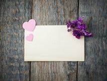 Coeur et fleurs de papier des violettes sur une vieille feuille de papier sur le fond en bois rustique Photo libre de droits