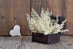 Coeur et fleurs disposés dans le coffre au trésor Photo stock