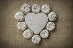 Coeur et fleurs faits en mache de papier sur un fond de tissu Images stock