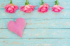Coeur et fleurs roses sur le bois de bleu de turquoise au rétro style Photographie stock libre de droits