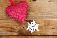 Coeur et flocon de neige rouges sur le fond en bois Image libre de droits