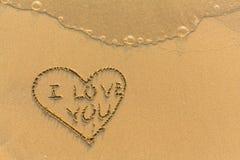 Coeur et je t'aime - tiré par la main en sable doux de plage de mer Résumé Image stock
