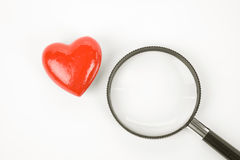 Coeur et loupe rouges Images stock