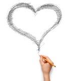 Coeur et main avec le crayon Images stock