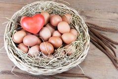 Coeur et oeufs rouges dans un panier Photographie stock libre de droits