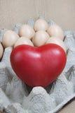 Coeur et oeufs sur le bois de papier de modèle Photographie stock