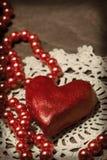 Coeur et perles d'argile sur le tissu tricoté Images stock