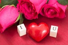 Coeur et roses rouges, et cubes en bois avec des lettres I et U Photographie stock libre de droits