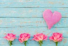 Coeur et roses roses sur le fond en bois bleu de vintage léger avec l'espace de copie Photographie stock