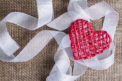 Coeur et ruban sur le fond de toile de jute Concept d'amour de mariage Photos libres de droits