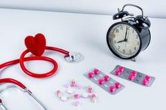 Coeur et stéthoscope rouges, réveil, drogues, pilules sur la table Images libres de droits