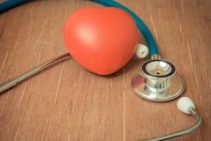 Coeur et stéthoscope rouges sur le fond en bois Images stock