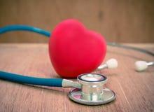 Coeur et stéthoscope rouges sur le fond en bois Photo stock